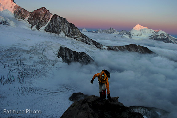 Climber above the clouds at sunrise